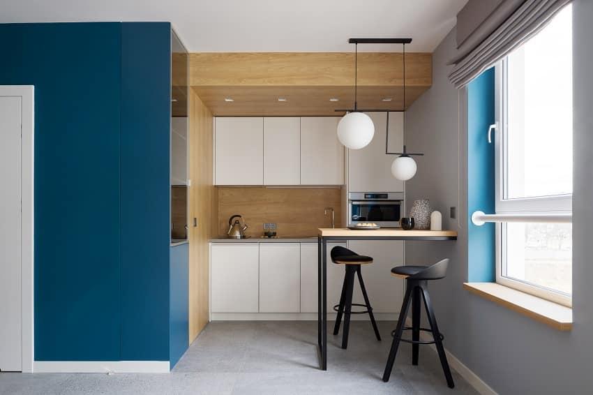 modern and small kitchen with console table two chairs wooden walls and gray floor tiles blue wall and window