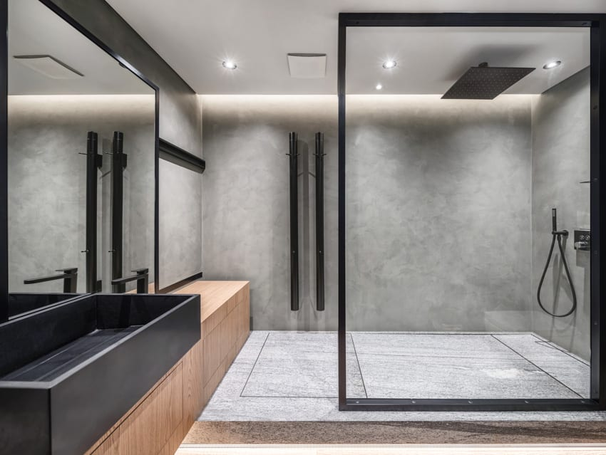 Modern bathroom with gray cultured marble walk in shower and wood bench