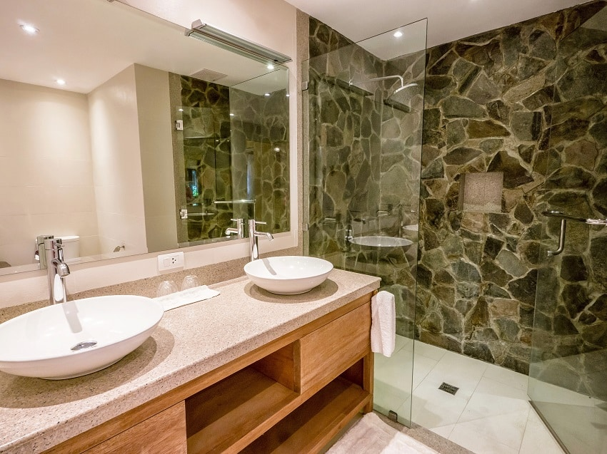 modern bathroom with two round white vessel sinks on granite counter natural stone and glass shower enclosure