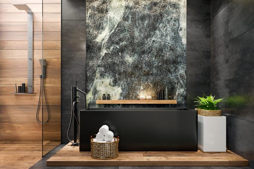 Modern bathroom with wood flooring in shower area and black bathtub