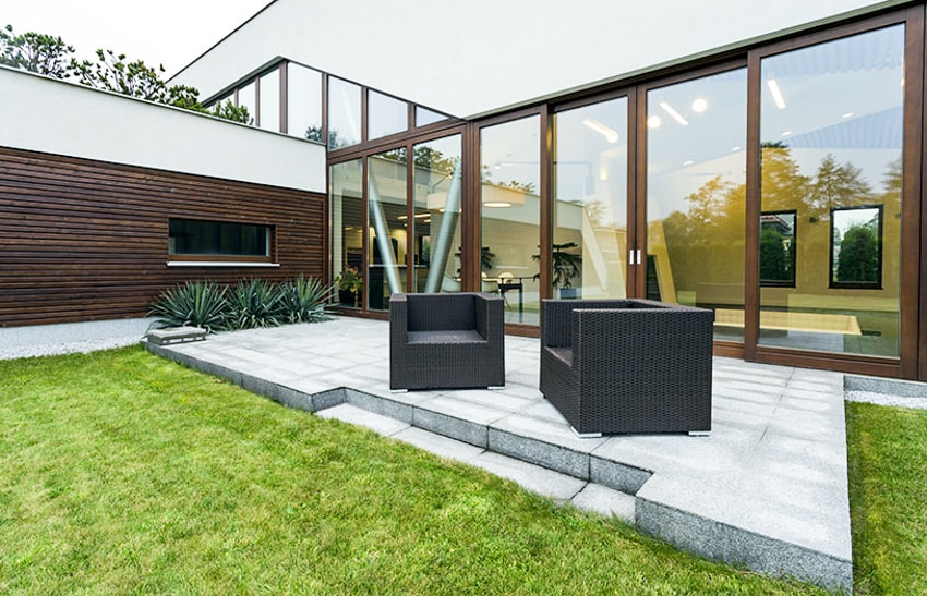 Modern concrete patio with glass folding door window wall rattan furniture and grass area