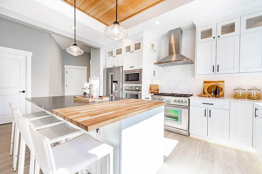 Modern farmhouse kitchen with butcher block wood countertops white cabinets wood ceiling feature