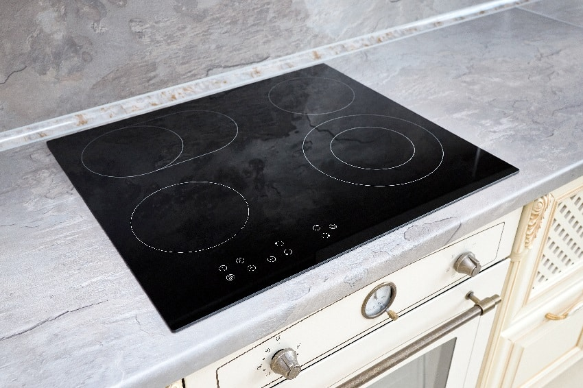 modern kitchen interior with black induction cooktop with marble countertop