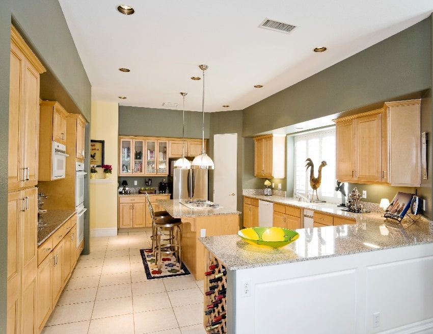 modern kitchen with gray wall paint oak wood cabinets and stools at the island