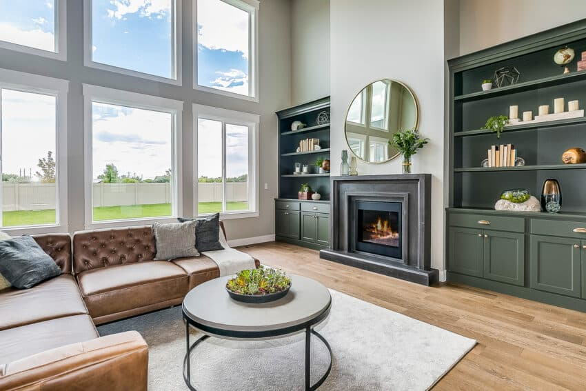 Modern living room with large windows sofa and green cabinets