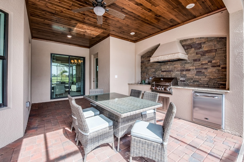 Modern outdoor kitchen and dining area with grill and hood