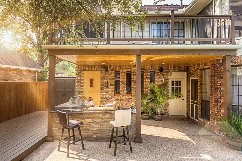 Modern outdoor kitchen with island stools grill in patio