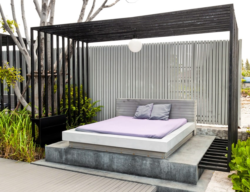 Modern pergola with outdoor lounging bed and overhead lighting