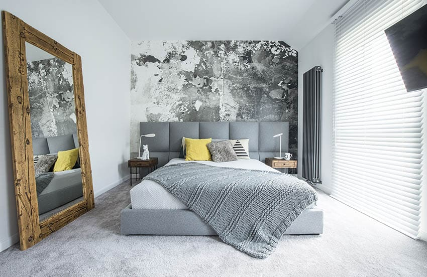 Modern platform bed with gray fabric patterned accent wall large wall mirror