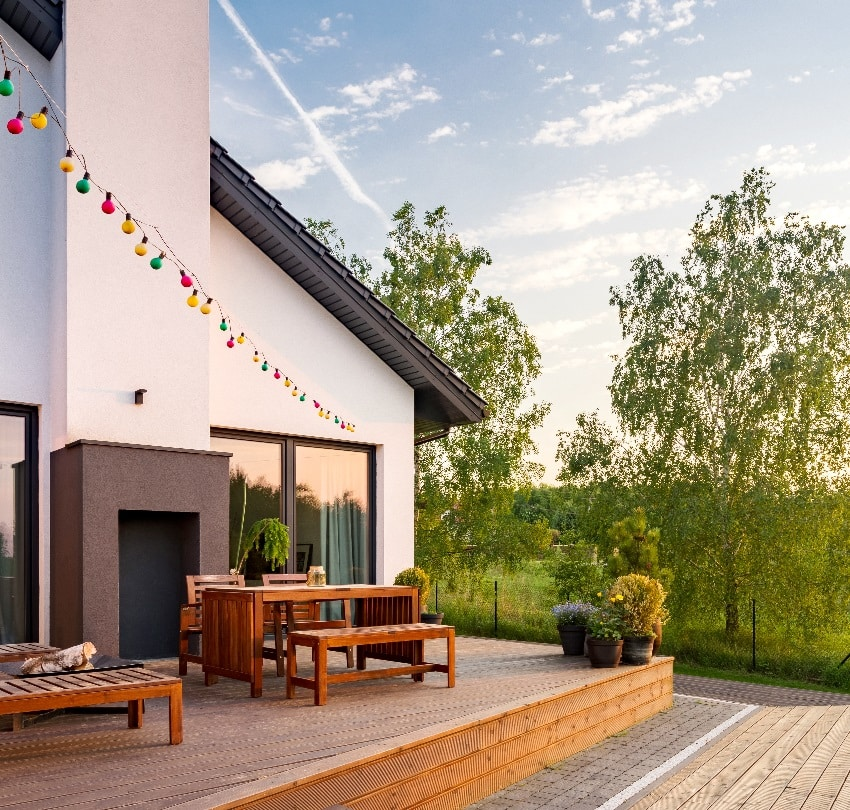Nice view of villa with outdoor wooden deck patio furniture and cute string lights