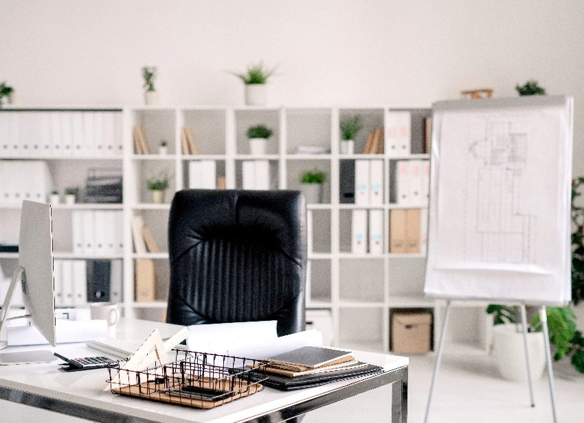 office room with desk, black leather armchair, whiteboard, computer monitor and other supplies on background of shelves with documents