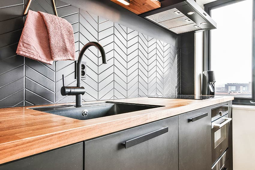 One wall kitchen with butcher block countertops black cabinets