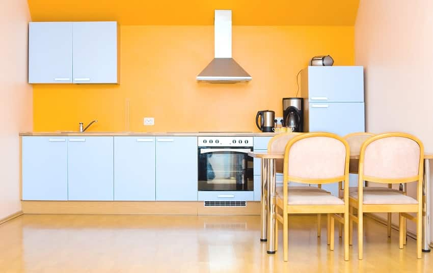 orange modern fitted kitchen with white cabinets yellow dining set and coffee maker