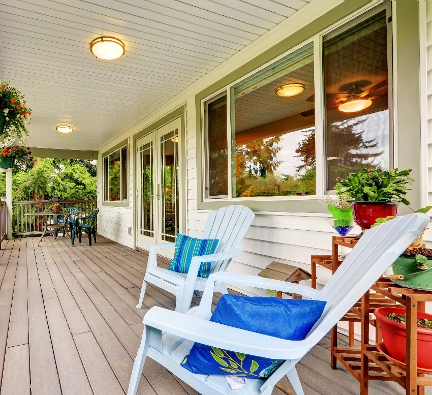 outdoor deck with railings outdoor seats flower pots and turned on lights on the ceiling