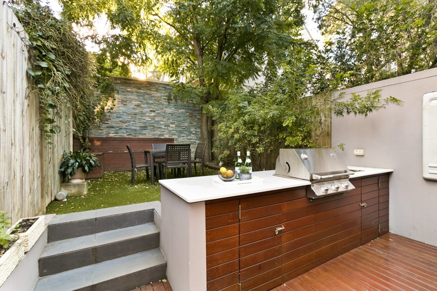 Outdoor kitchen with grill in backyard dining area