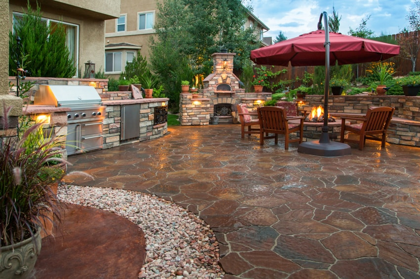 Outdoor kitchen with stone fire pit dining area and grill