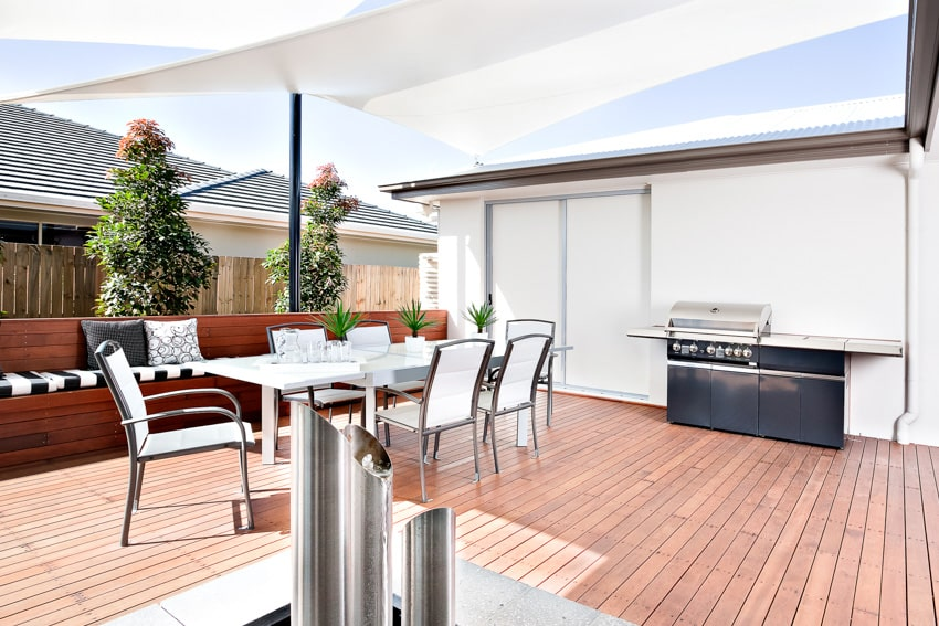 Outdoor patio with chairs tables and grill