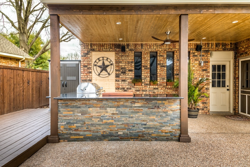 Outdoor patio with grill countertop and brick wall