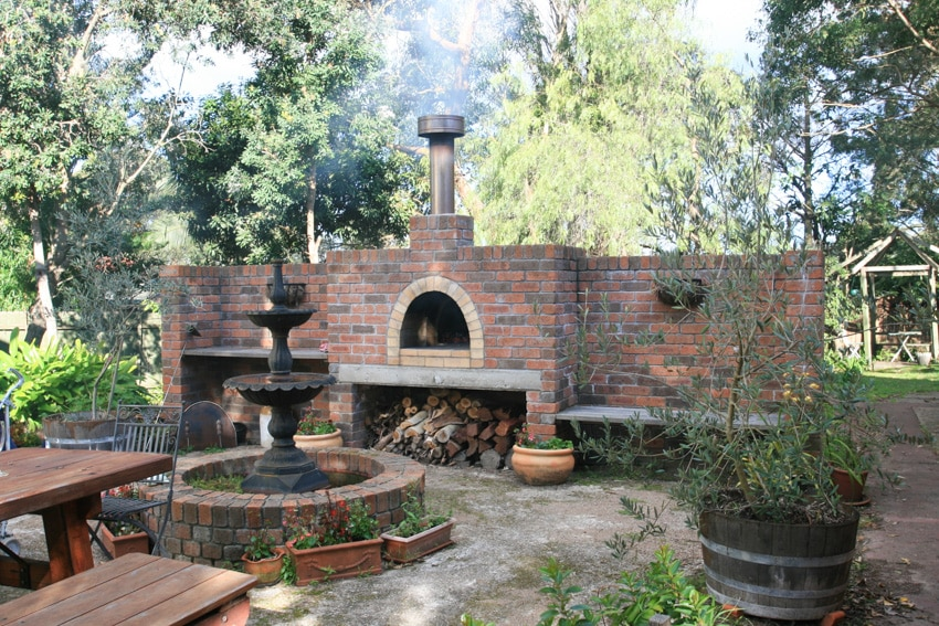 Outdoor pizza oven with old fountain and trees