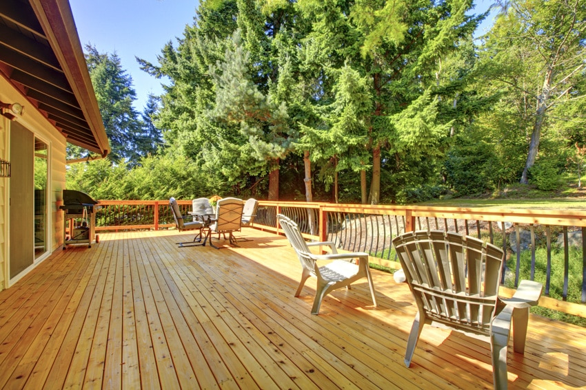 Outdoor wood deck with furniture and trees