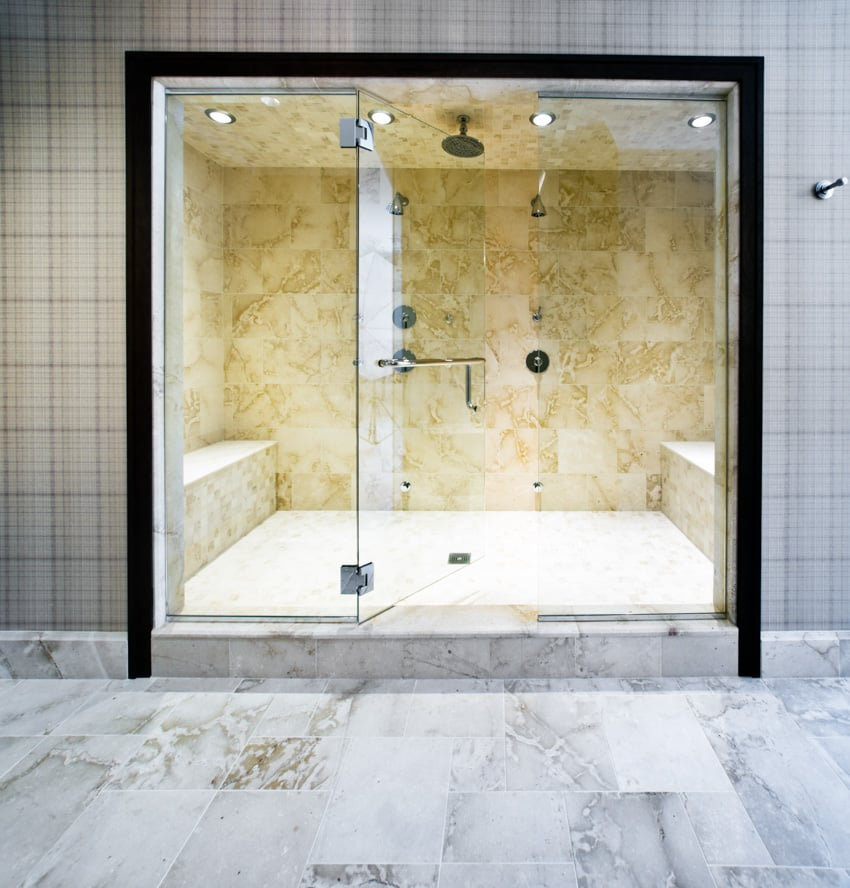 Pair of marble built in shower benches and a glass door