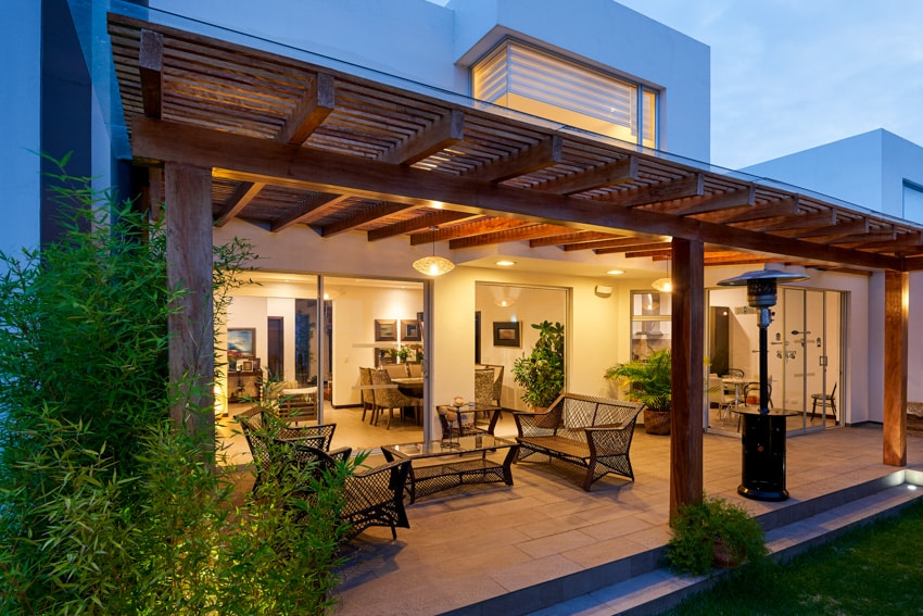 Patio pergola in backyard of home with hanging lights