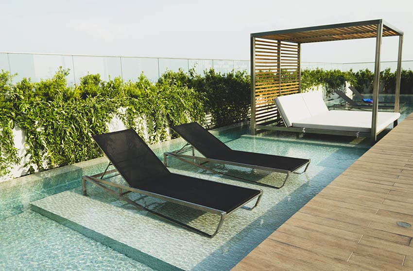 Plunge pool with in water lounge chairs day bed with pergola