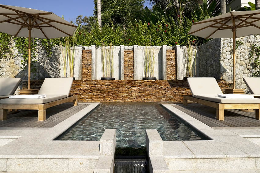 Plunge pool with water feature stacked stone accent wall