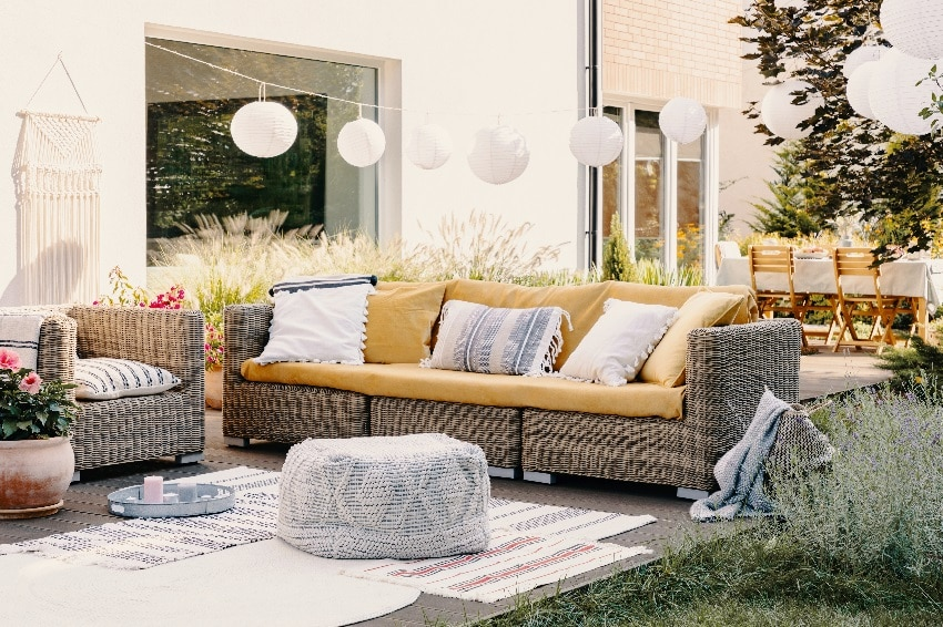 pouf next to rattan couch and armchair on wooden deck with lantern lights and flowers