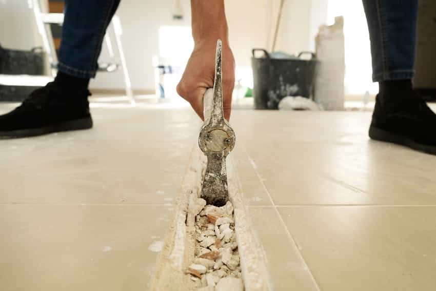 Removing tile flooring with hammer