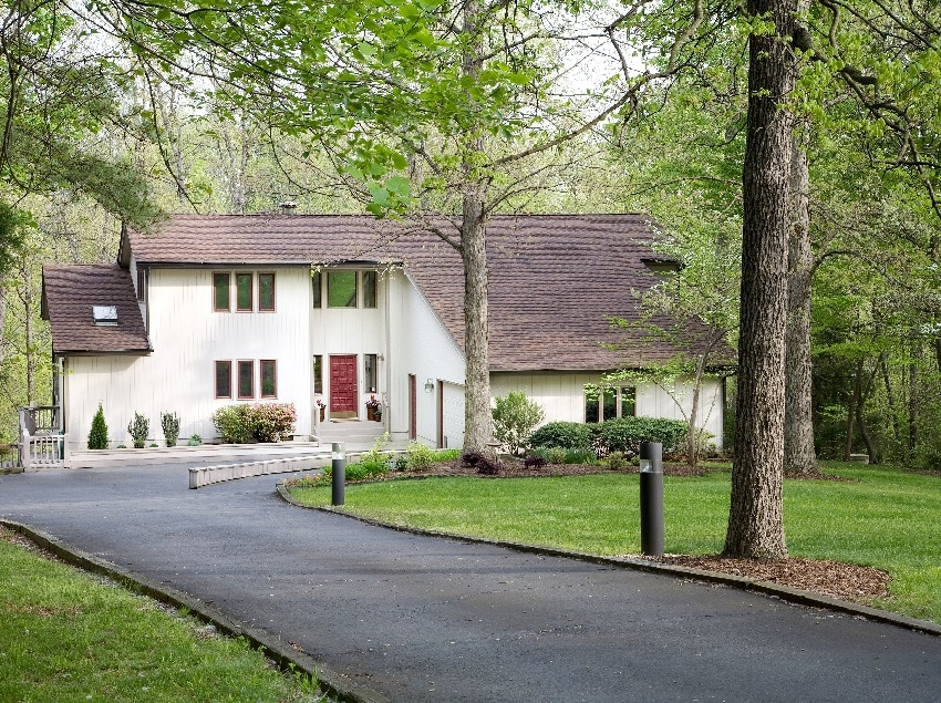 residential home with asphalt driveway surrounded with grass and trees