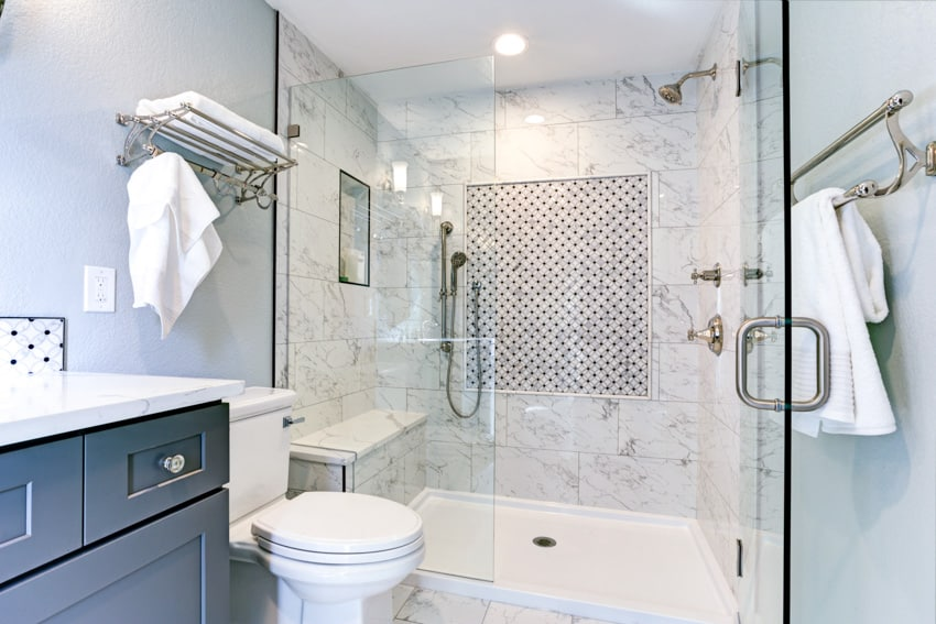 Shower bench in tiled bathroom with toilet and cabinet