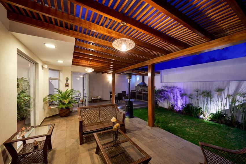 Slatted wood pergola shade in backyard patio