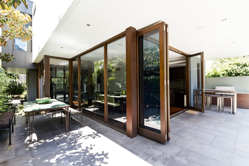 Sliding folding patio door with large windows and outdoor furniture