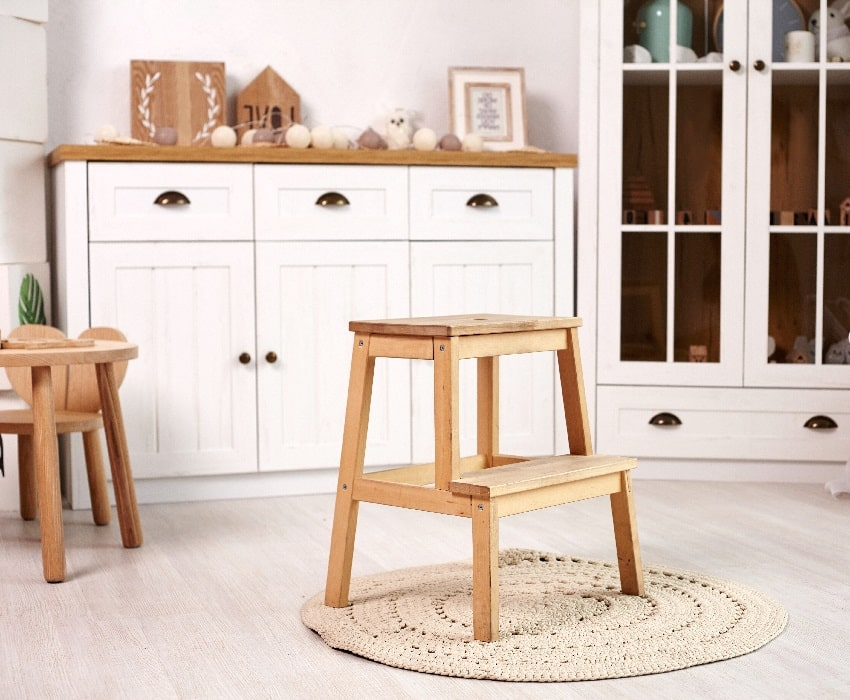 Small cute heart shaped chair and table little wooden ladder on a round rug with pads in the middle of the room