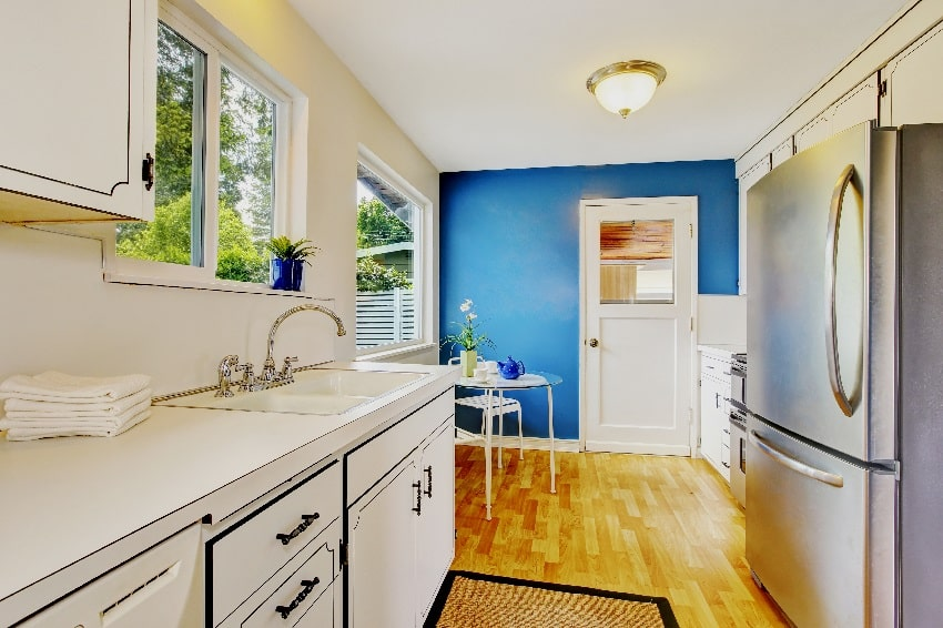 small kitchen room interior with white cabinets navy blue walls and glass dining table