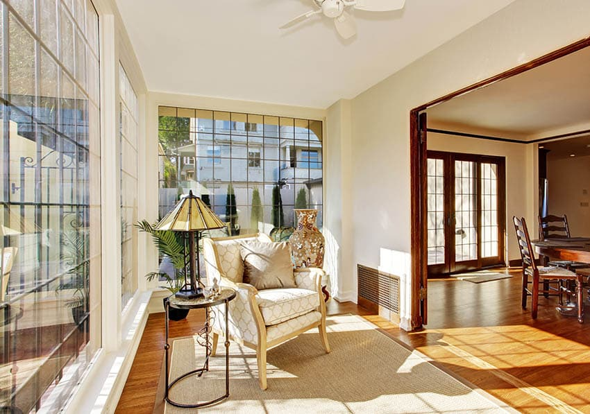 Small sunroom with white ceiling cream painted walls light color flooring