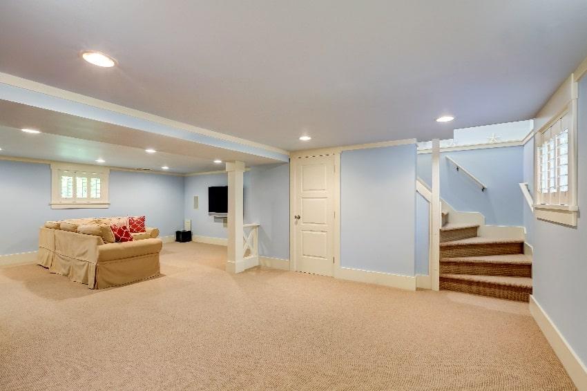 spacious basement room interior in pastel blue tones and beige carpet floor