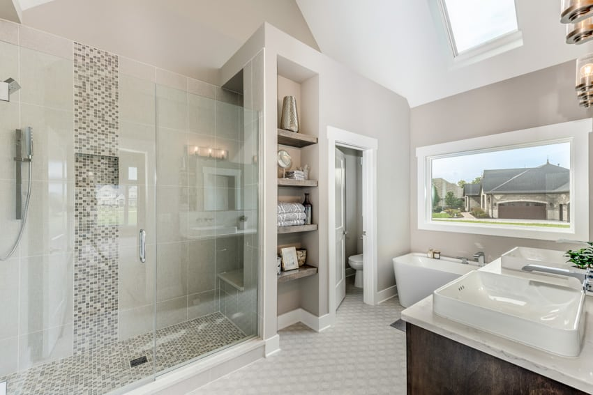 Spacious bathroom with shower area bench sink toilet and shelves