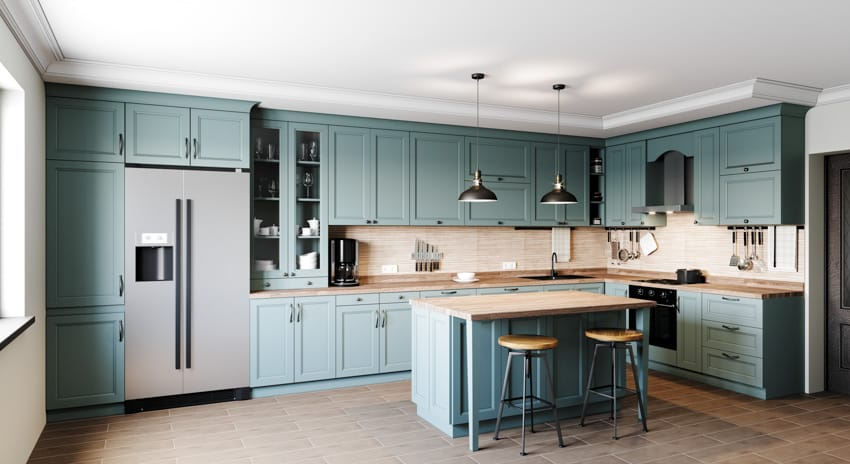 Spacious kitchen with green cabinets wood countertop island stools overhead lights and refrigerator