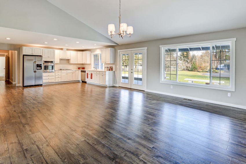 Spacious room with laminate flooring ceiling light and appliances