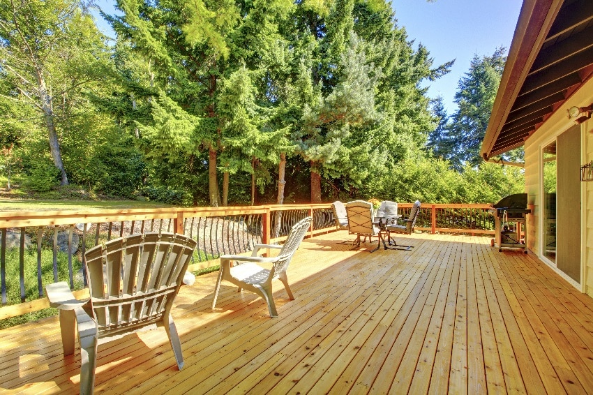 Spacious wooden ipe deck with patio area plastic chairs and beautiful view