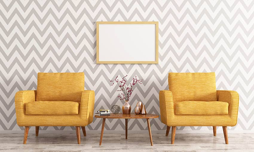 Striped wallpaper in living room with yellow arm chairs