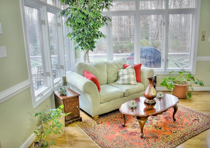 sunroom with plants and some antique furnitures