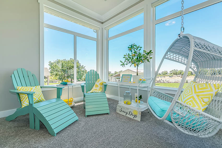 Sunroom with pops of color teal furniture cushions swinging chair