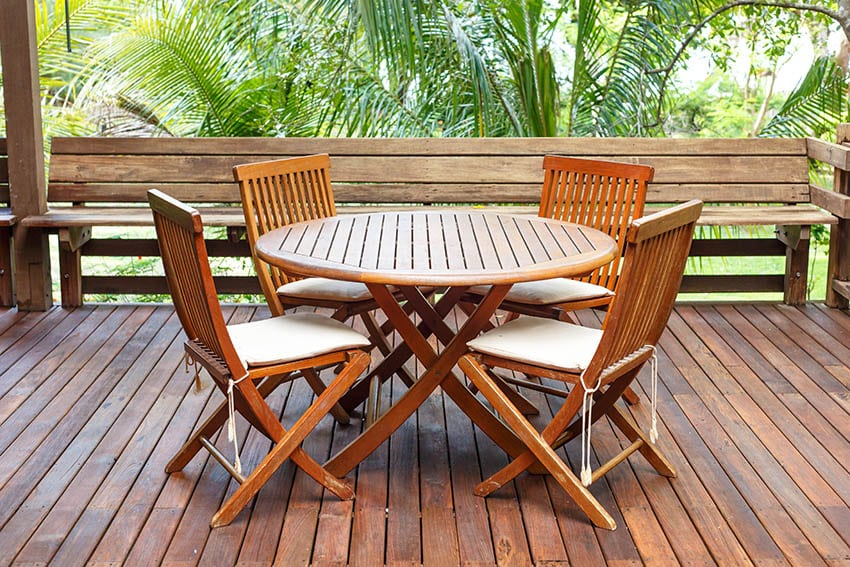 Teak outdoor furniture table chairs on deck