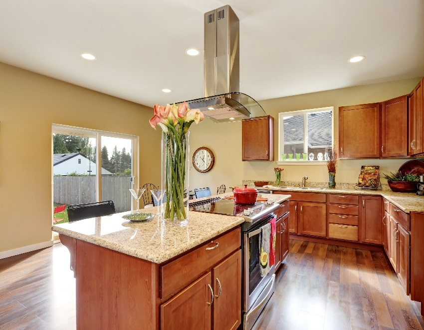traditional american kitchen with warm beige wall paint stainless steel appliances and vase with flowers on the island countertop