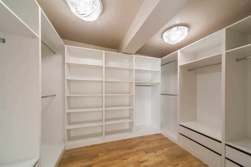 Walk-in closet built in storage shelving wood floor