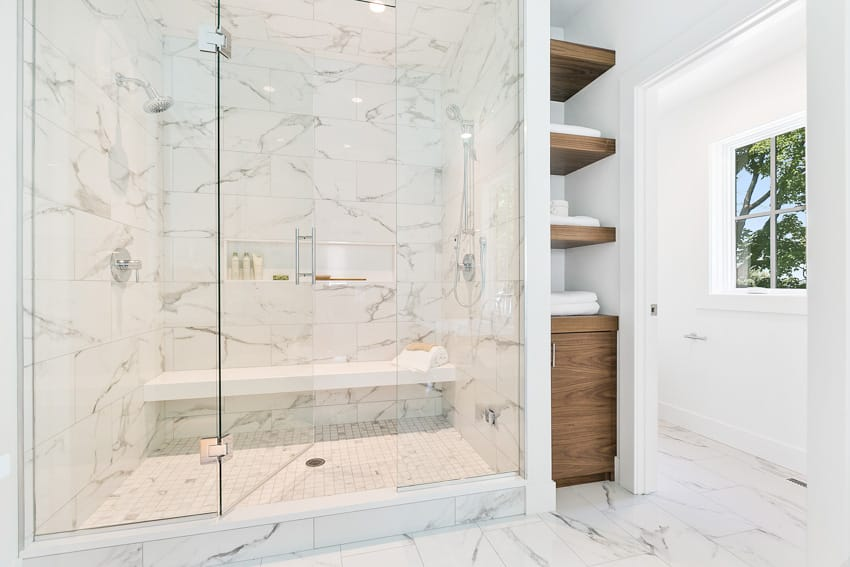 White bathroom with shower bench glass door and wood shelves