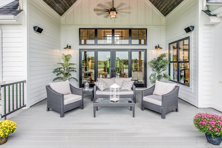 White house with folding patio door ceiling fan and outdoor furniture